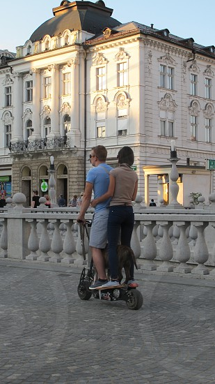 couple man woman dog motorized skateboard bridge famous triple Ljubljana Slovenia transportation fun destination tourist photo