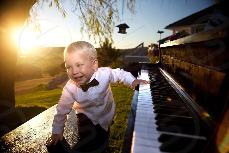 A young maestro having fun at the piano as the sun sets over the San Juan Islands in Washington.  photo