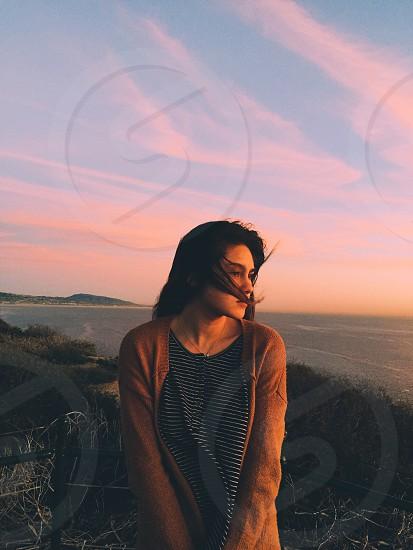 woman in brown cardigan standing beside black steel railings looking sideways near ocean during sunset photo