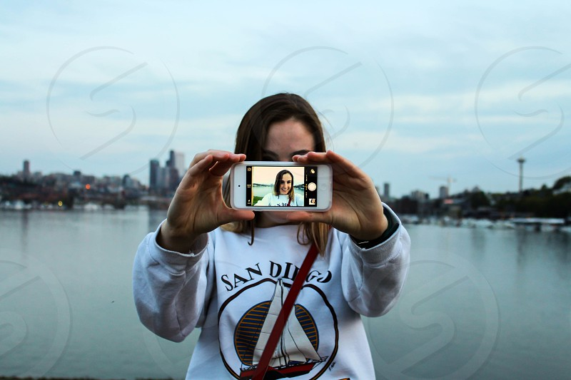 woman wearing white sweatshirt holding white iphone photo