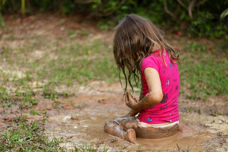 girl in pink t shirt sitting on mud soil photo
