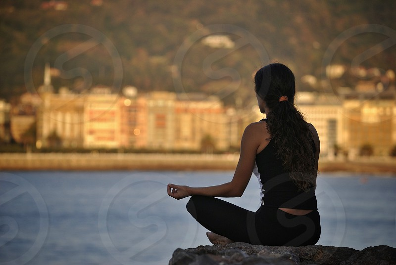 woman meditating during day time photo