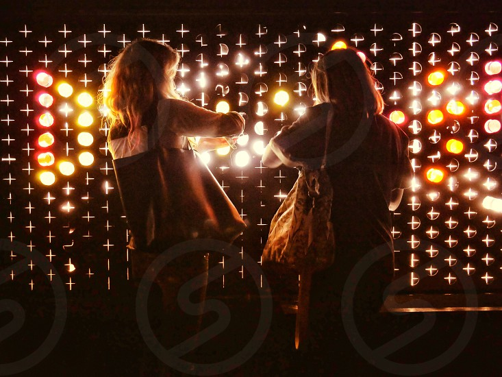 Two young women playing with a light art exhibit at the Color Factory in San Francisco California  photo