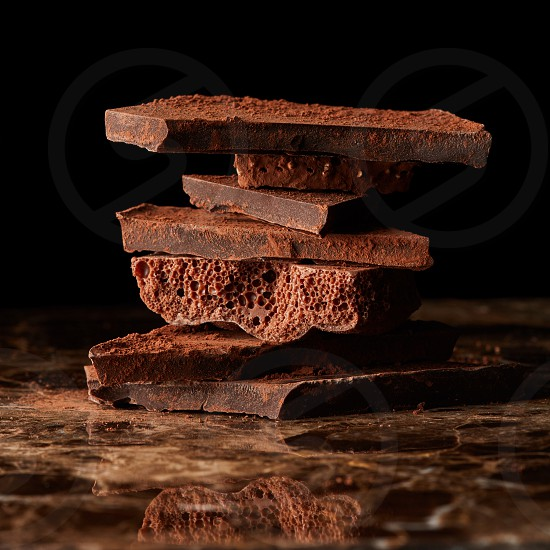 Heap of broken pieces of chocolate on a dark marble background photo