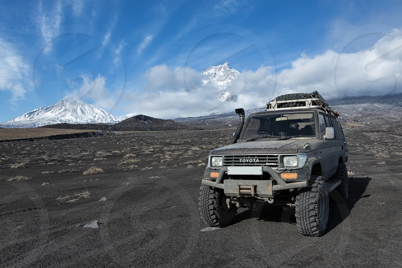 KAMCHATKA PENINSULA RUSSIA - OCT 1 2016: Japanese 4wd car Toyota Land Cruiser Prado prepared for long travel and off-road tourism through mountains parked on volcanic slag on background volcanoes. photo