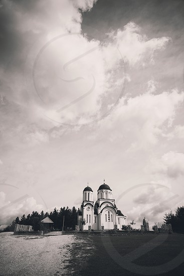 Exterior of a small Orthodox church on the hill in black and white.  photo