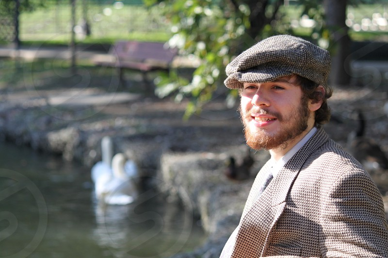 Man with beard relaxing by a pond in springtime  photo