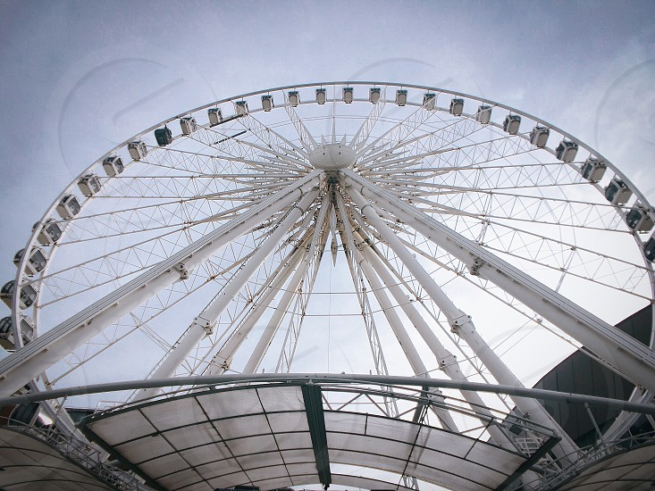 worm's eye of white ferris wheel under the white and blue cloudy skies during daytime photo