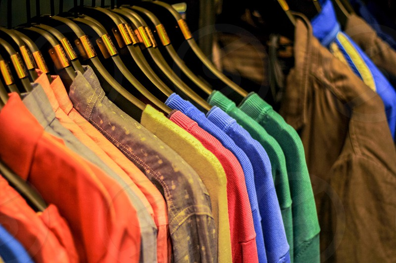 mixed shirt and jackets on black plastic cloth hangers hanging on cloth line photo