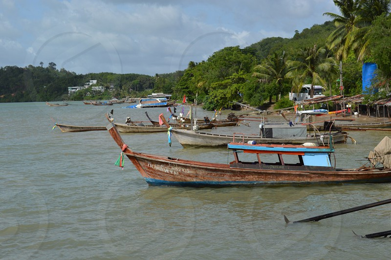 brown fishing boat on water parked beside green trees photo