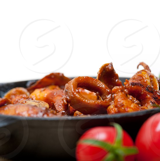 fresh seafood stew prepared on an iron skillet ove white rustic wood table  photo