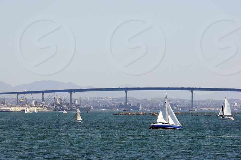 Sailboats in the harbor in San Diego California with the Coronado Bridge in the background photo