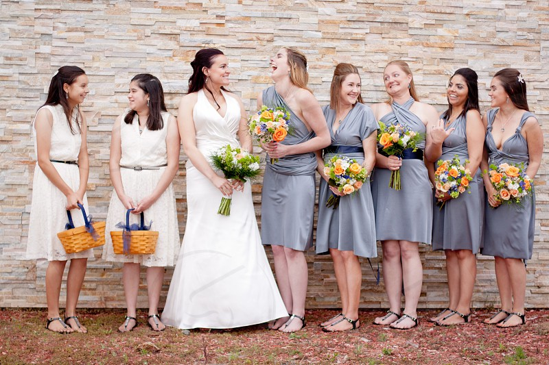 bridge flower girls and bridesmaid standing side of side standing in front beige concrete wall during daytime photo