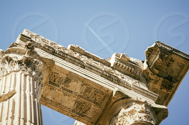 Close-up of portico of Octavia in Rome Italy with airplane flying overhead photo