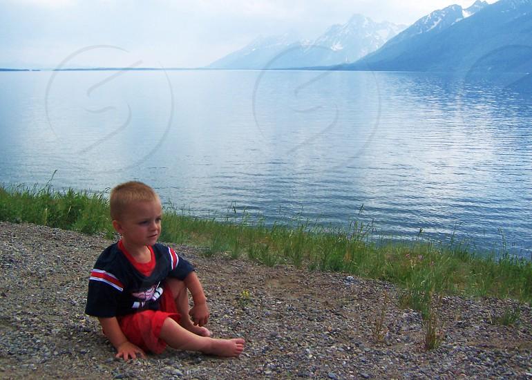 boy sitting near big river photo