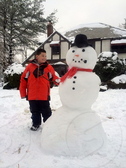 A young boy and his snowman  photo