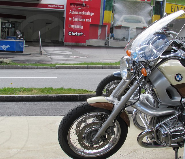 grey brown and white bmw motorcycle parked on parallel with motorcycle on white and black ground near road between green short grass in front of white and red building photo