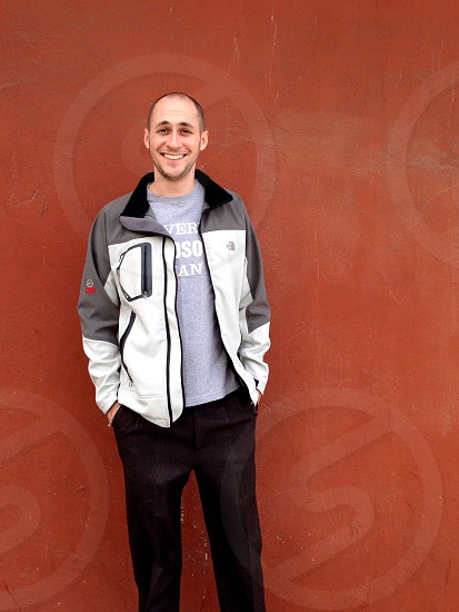 man in white and gray jacket and black pants smiling on a brown wall background photo