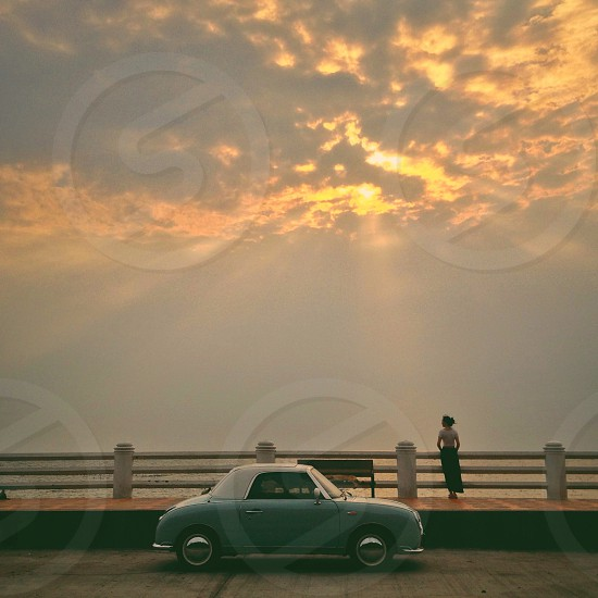 mint green and white 2 door car alongside beach at sunset  photo