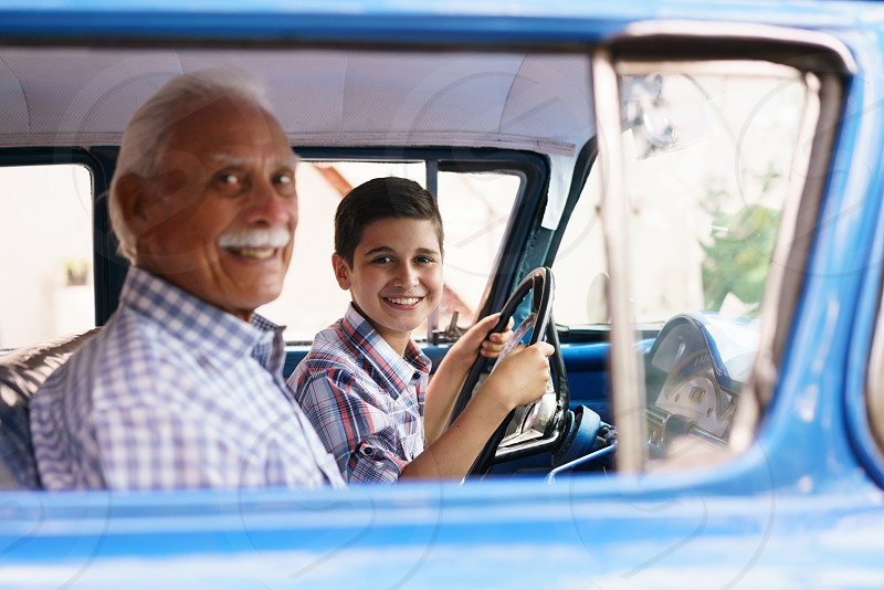 grandpa boy car drive class lesson driving affection american auto automobile cheerful cuban child driver elderly enjoy excited family generation gap grandchild grandfather grandson happy hispanic kid learning man old playing people portrait practice retired retirement senior smile smiling steering teaching together transportation two people vehicle vintage wheel young photo