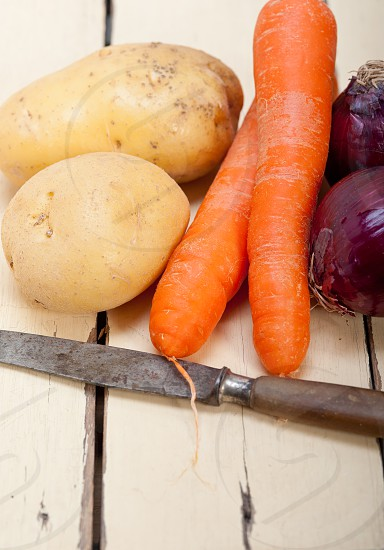 basic vegetable ingredients carrot potato onion on a rustic wood table photo