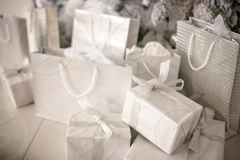 gifts boxes and packages under the luxurious festive decor of the Christmas tree with garlands for the festive holiday. Background of a happy new year and the atmosphere of comfort. photo