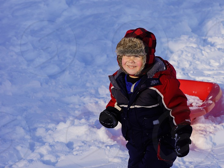 Little boy smiling pulling sled coat hat mittens winter snow  photo