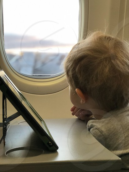 Baby child boy looking airplane aircraft window airport photo