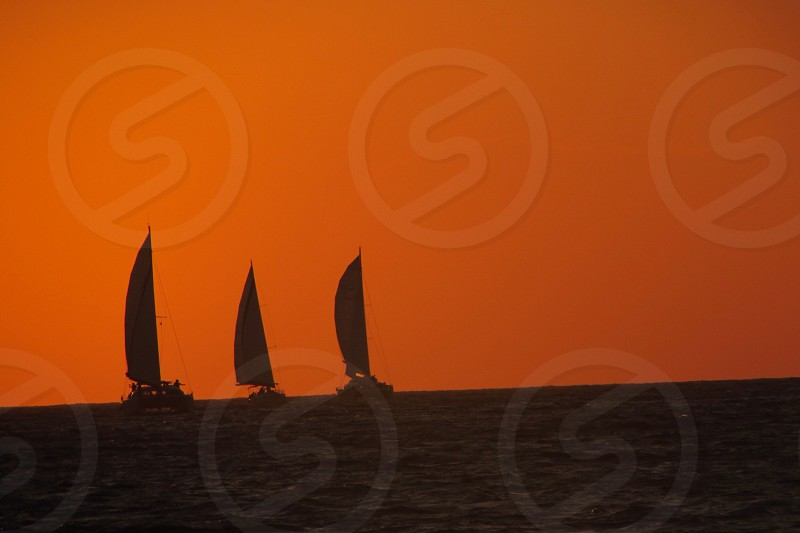 Sailboats in the sunset off Santorini Greece photo