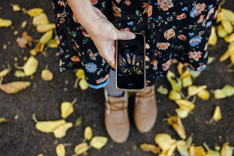 Woman takin a photo of her feet in suede boots surrounded by yellow fallen leaves photo