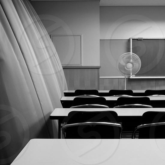 white pedestal fan in front of blackboard photo