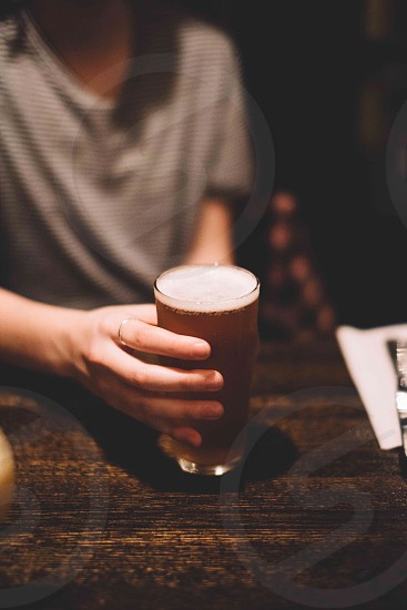 person holding beer in clear drinking glass photo