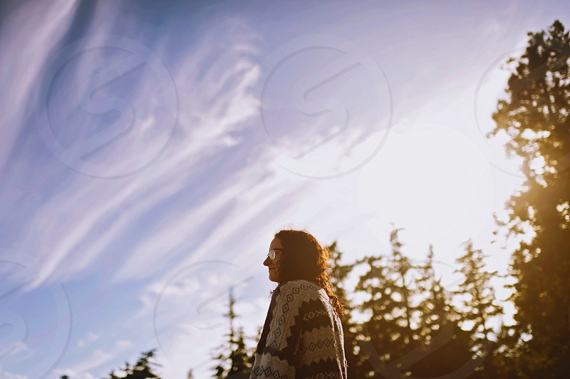 woman in beige and black tribal shirt by green pine trees under blue sky photo