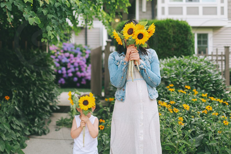 A mother and son holding up sunflowers.  photo