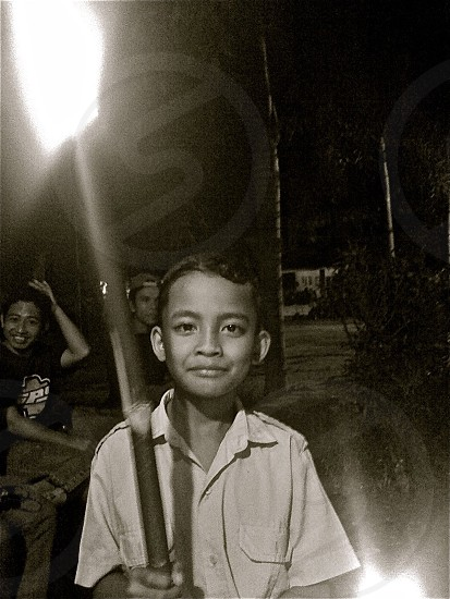 lifestyle people travel religion Bali. Young Balinese boy with torch helps light the way during a night ceremonial procession. photo