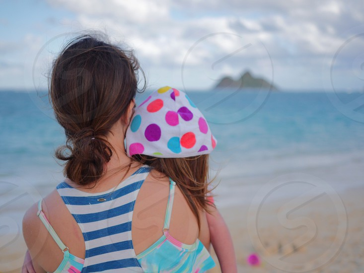 shallow focus photography of woman in girl sitting near beach side during daytime photo