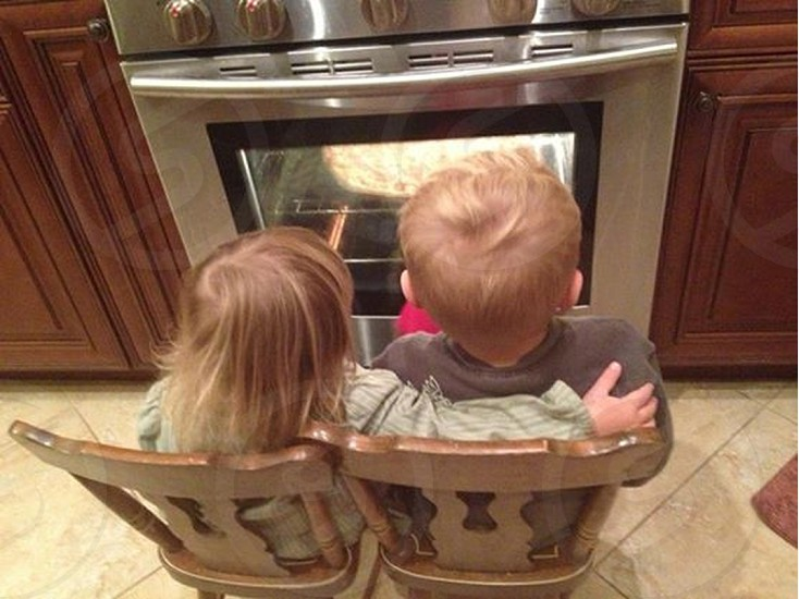 boy and girl sitting in front of oven photo