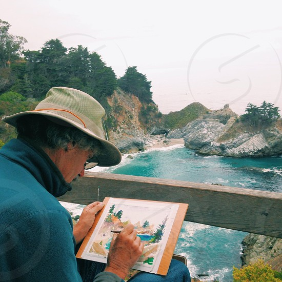 person painting on wood bridge overlooking river with boulder photo