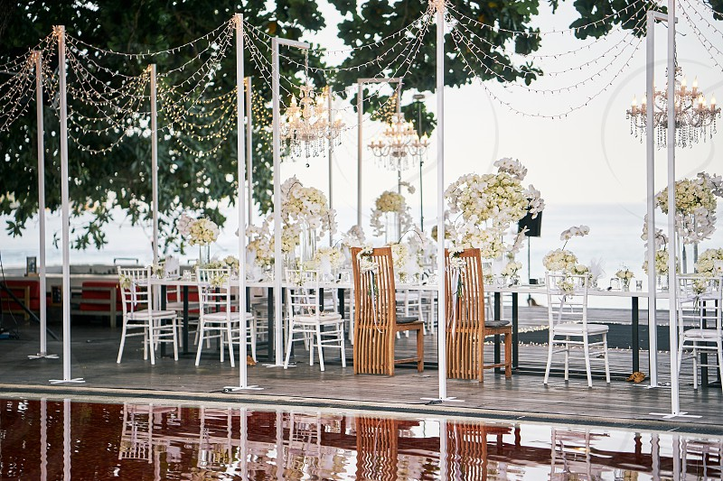 Luxury wedding reception dinner venue setting for celebration with the white roses flower theme A bunch of white roses flower floral decoration on the dinner table photo