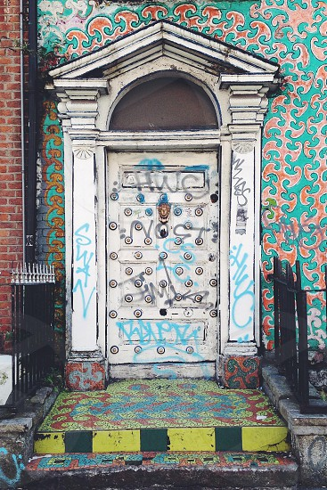 graffiti on white wooden door with arch photo