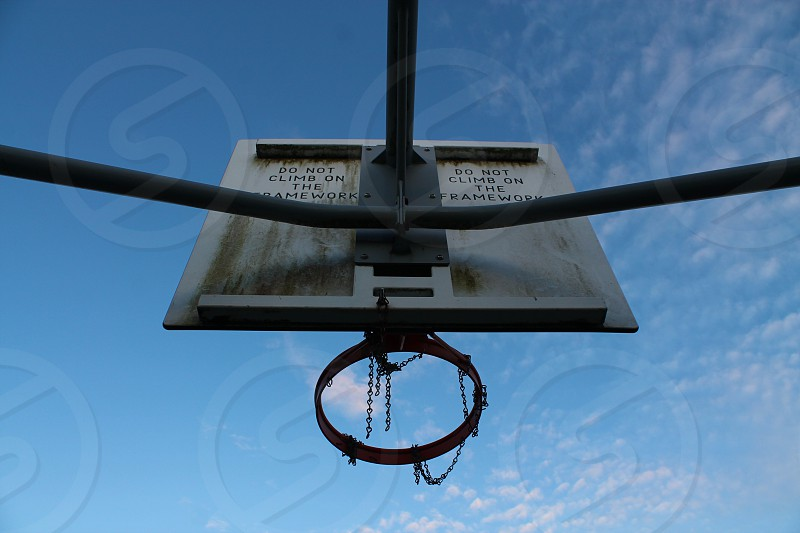 Basket ball basket sport game outdoors no people abandoned behind from under from undet steel dirt dirty used left alone target goal tall high unique angle different hidden behind sky blue clouds small low angle view low angle view sunny sunlight sun summer fun activity active leisure time leisure activity ball photo