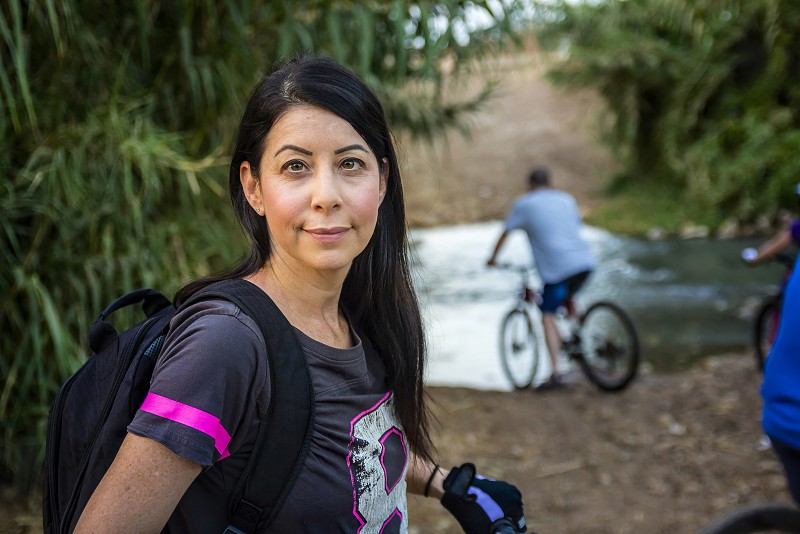 Woman riding a bicycle in the countryside and looking at camera. photo