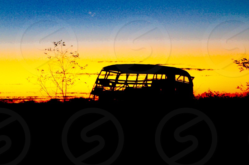 Wrecked double decker bus abandoned to the Australia Outback creates a haunting silhouette against the golden sunset photo
