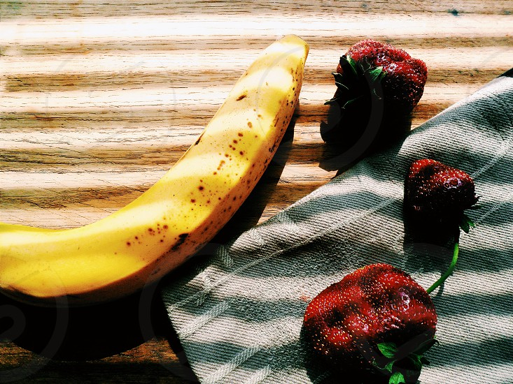 banana and strawberry on top of brown wooden platform photo