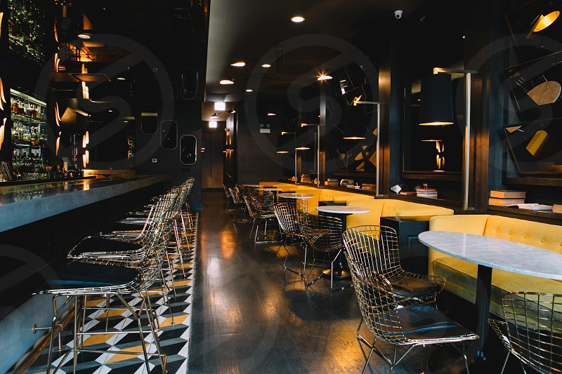 bar with black and yellow sofa white table stainless steel chairs white lamps and wall mirror photo
