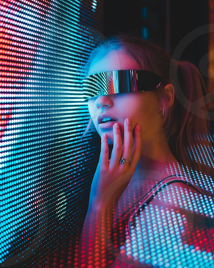 Futuristic shot of girl wearing shades with lines of light surrounding photo