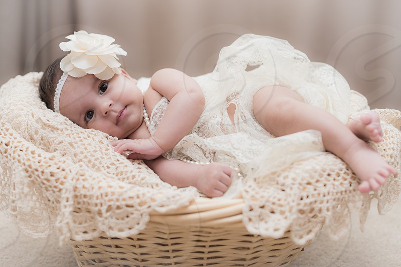 baby lying on brown wooden baby bed photo