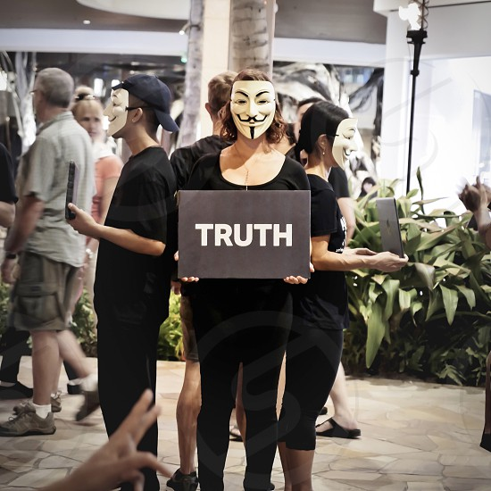 Anonymous activists people with musks protests in the street  photo