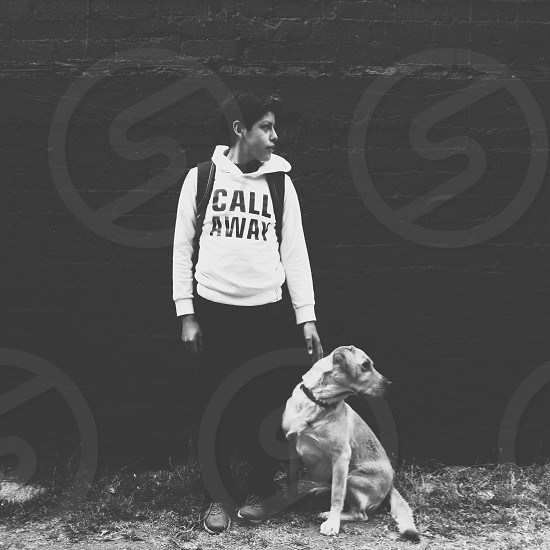 boy in black call away printed white hoodie standing beside white short haired large dog sitting photo