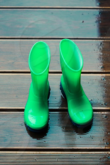 Blue wellies standing on a wooden porch while raining photo